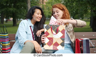 Pretty girls showing purchase in shopping bags chatting ...