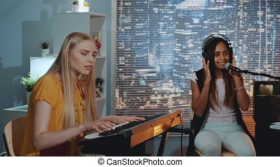 Pretty girls singing a song while one of them playing the keyboard during rehearsal at home