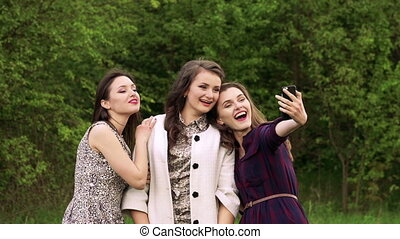 Pretty girls taking selfie in green garden. Slowly