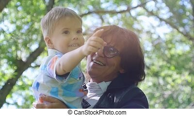 Pretty grandmother wearing glasses and little grandson enjoying sunny day in the park in slow motion. Happy childhood. 1920x1080