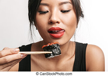 Pretty happy asian woman sitting isolated