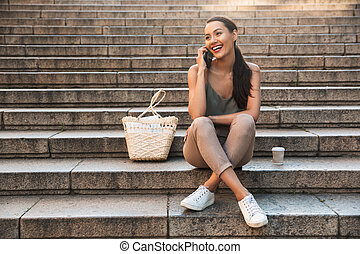 Pretty happy asian woman sitting on steps