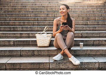 Pretty happy asian woman using mobile phone.