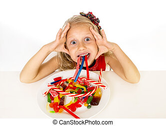 pretty happy Caucasian female child eating dish full of candy in sweet sugar abuse dangerous diet