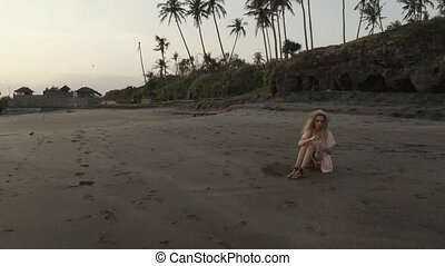 Pretty happy girl in dress relaxing on the tropical beach....