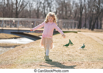 Pretty happy girl in pink jacket, cute skirt and warm pantyhose runs and scares the birds on sunny day in the city park alone
