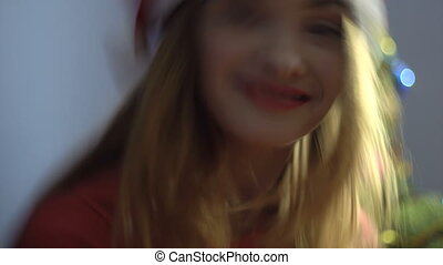 pretty happy girl in santa hat smiling on camera. christmas mood
