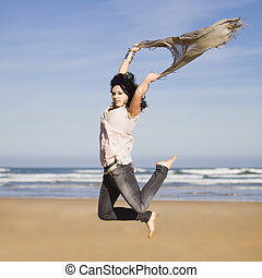 beautiful happy young girl running and jumping over a windy beach with a blowing scarf