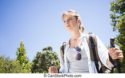 Pretty hiker with backpack walking uphill