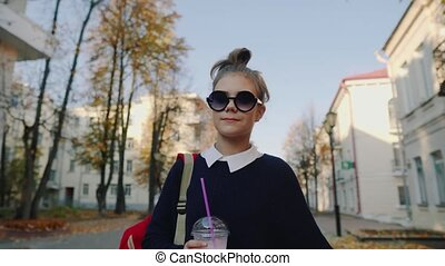 Pretty hipster teen with red bag drinks milkshake from a...