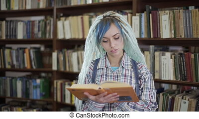 Pretty hipster woman choosing book for reading on leisure...