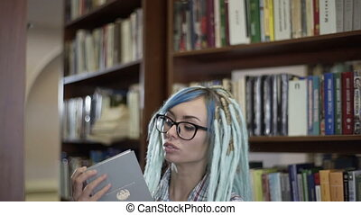 Pretty hipster woman in glasses with dreadlocks choosing...