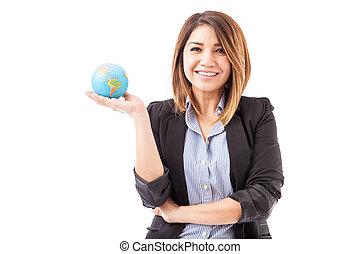 Pretty Hispanic businesswoman with a globe