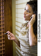 Pretty Hispanic woman talking on a mobile phone - Close up...