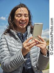Pretty hispanic woman with mobile make self-portrait in a sunny day in Barcelona