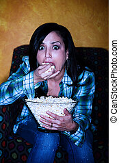 Pretty Hispanic woman with popcorn watching television