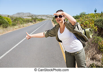 Pretty hitchhiker sticking thumb out on the road on a sunny day