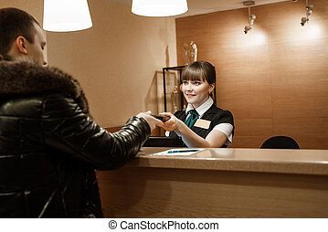Pretty hotel receptionist giving key to male guest