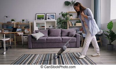 Pretty housewife cleaning carpet with vacuum cleaner dancing...