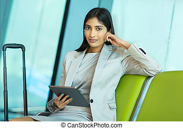 indian business traveler at airport using tablet computer