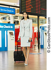indian businesswoman standing next to flight information board
