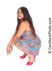 Pretty Indian woman crouching.