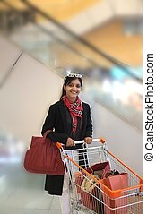 Pretty Indian woman with trolley after shopping in a mall.