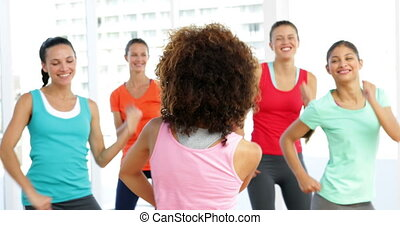 Pretty instructor leading zumba class in fitness studio