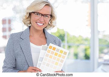 Pretty interior designer holding up colour samples in bright...
