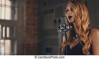 Pretty jazz vocalist in dress perform on stage at microphone. Dark make up.