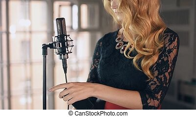 Pretty jazz vocalist in dress with bright make up on stage at concert microphone