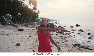 Pretty joyful brunette woman playing with soap bubbles on tropical beach at sunset time. slow motion.