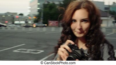 Girl with retro camera smiling in the street