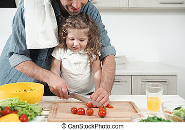 Pretty kid watching her father making salad