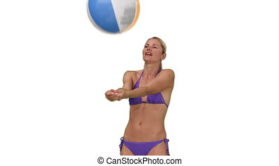 Pretty lady in purple swimsuit playing with a beach ball