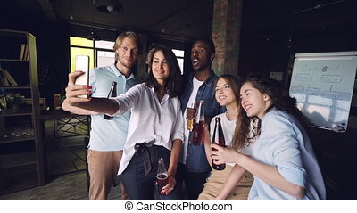 Pretty lady is taking selfie with colleagues using...