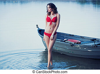 Pretty lady posing next to the boat