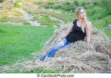 Pretty lady posing sitting on the hay.