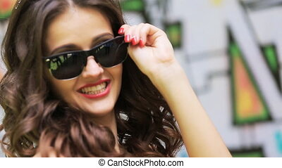 Pretty lady putting on the sunglasses on graffiti background