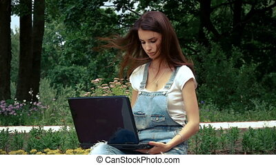 pretty lady with dark hair looks in a laptop in the summer...