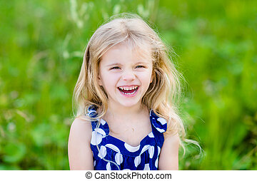 Pretty laughing little girl with long blond curly hair