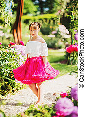 Pretty little 9-10 year old girl playing in beautiful garden, wearing bright pink tutu skirt