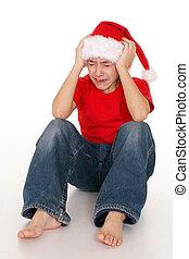 boy in santa hat crying