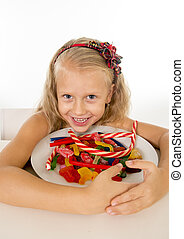 pretty little female child eating dish full of candy caramel and sweet food in sugar abuse and unhealthy diet