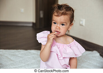 Pretty little girl child sitting on bed indoors