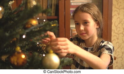 Pretty little girl decorates the Christmas tree.