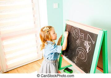 Pretty little girl drawing with chalk on a blackboard
