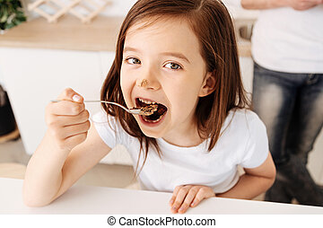 Pretty little girl eating a chocolate cake