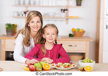 Pretty little girl helping prepare a fruit salad - Beautiful...