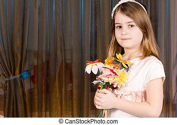 Pretty little girl holding flowers
